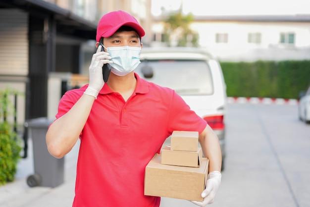 Pracownik pocztowy przenosi pudełko i staje przed domem i dzwoni do klienta za pomocą smartfona