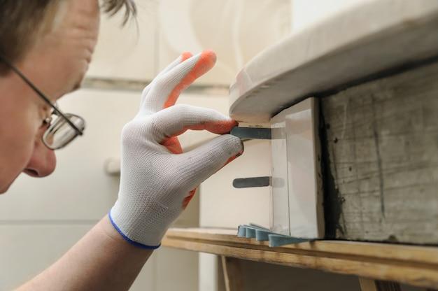 Pracownik podpiera płytkę.