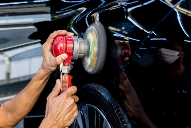 Pracownik poleruje samochód za pomocą narzędzia elektrycznego.