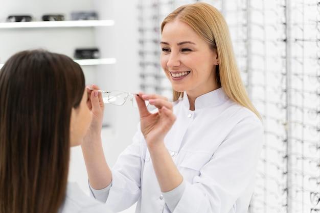 Pracownik pomaga dziewczynie przymierzyć okulary