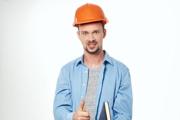 Pracownik pomarańczowy kask inżynier bezpieczeństwa na białym tle