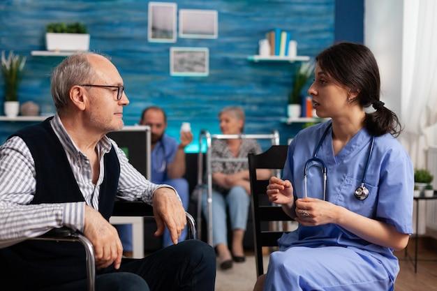 Pracownik pomocniczy wyjaśniający niepełnosprawnemu starszemu mężczyźnie leczenie zdrowotne