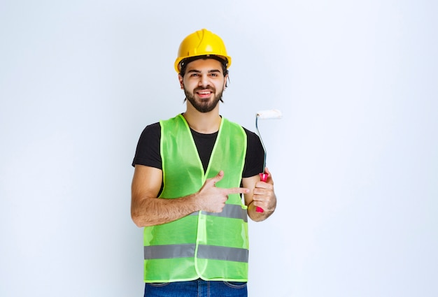 Pracownik posiadający biały wałek do malowania ścian.