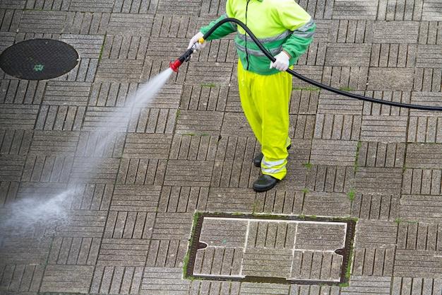 Pracownik posiadający wąż do czyszczenia chodnika wodą. koncepcja konserwacji miejskiej lub sprzątania