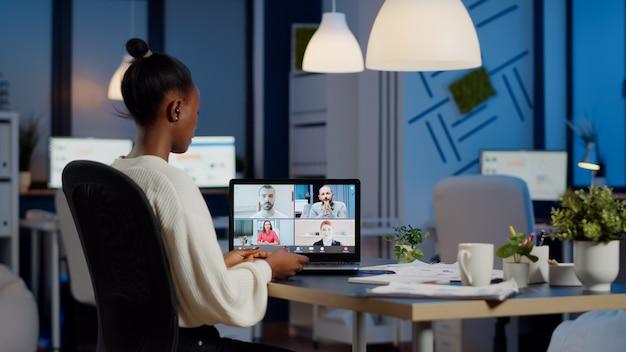 Pracownik pracujący w godzinach nadliczbowych w biurze firmy późno w nocy, dyskutujący z partnerami online za pomocą kamery internetowej