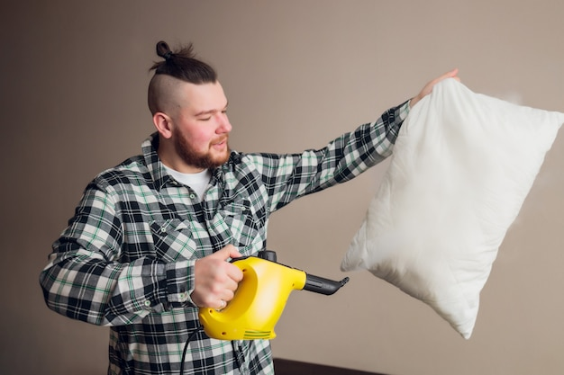 Pracownik pralni chemicznej usuwający brud z poduszki sofy w pomieszczeniu.