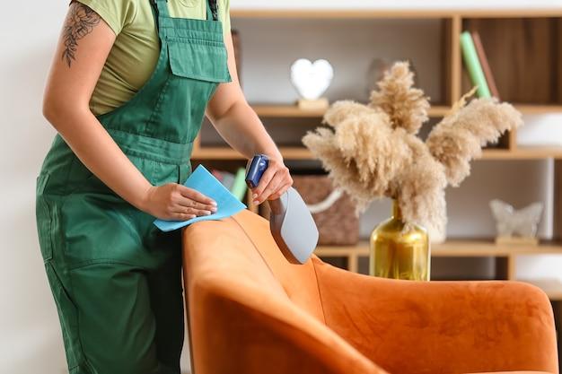Pracownik pralni chemicznej usuwający brud z sofy w domu