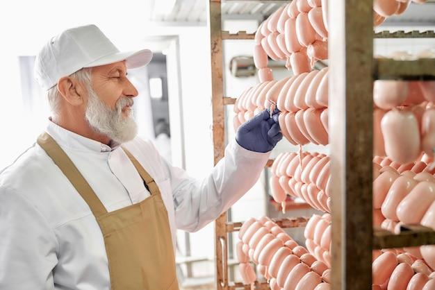 Pracownik produkcji fabryki mięsa obserwujący kiełbasy.