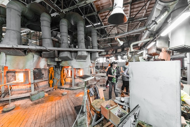 Pracownik produkcji szkła pracujący z wyposażeniem przemysłowym w fabryce