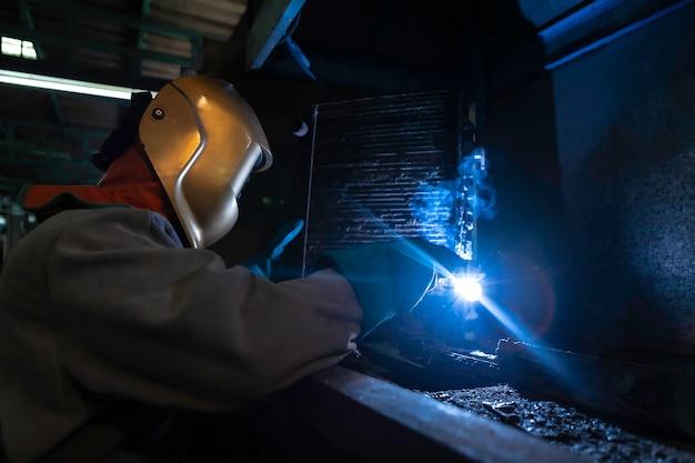 Pracownik przemysłowy przy spawaniu fabrycznym.