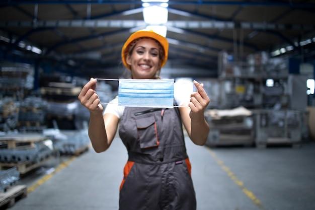 Pracownik przemysłowy stojący w hali fabrycznej i pokazujący maskę higieniczną jako ochronę przed wysoce zaraźliwym wirusem koronowym