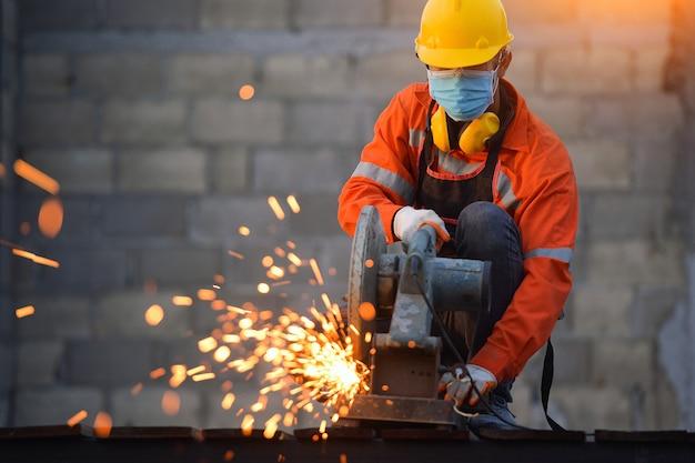 Pracownik przemysłowy tnący i spawający metal wieloma ostrymi iskrami, pracownik tnący metal szlifierką. iskry podczas szlifowania żelaza