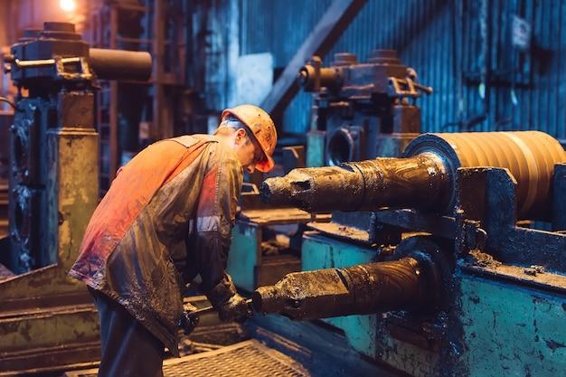 Pracownik przemysłu ciężkiego ciężko pracuje na maszynie. szorstkie środowisko przemysłowe.