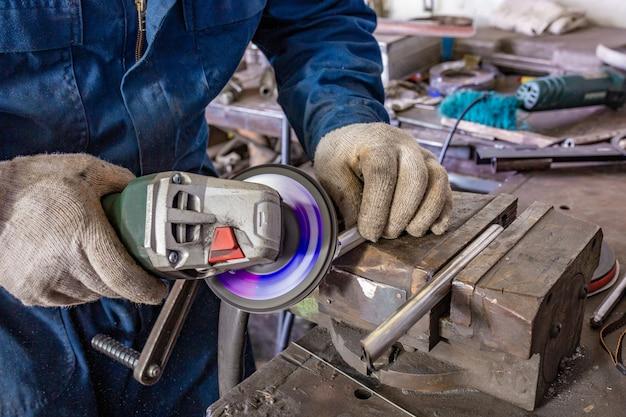 Pracownik przemysłu ciężkiego tnąca stal z szlifierką kątową w serwisie samochodowym