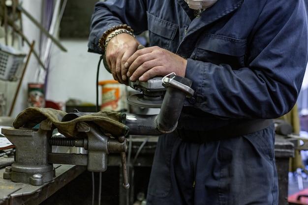 Pracownik przemysłu ciężkiego tnący stal szlifierką kątową w serwisie samochodowym.