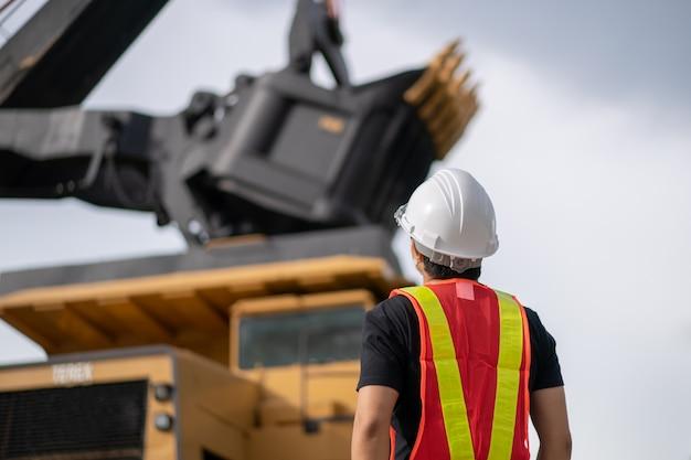 Pracownik przy wydobyciu węgla brunatnego lub węgla z ciężarówką przewożącą węgiel.