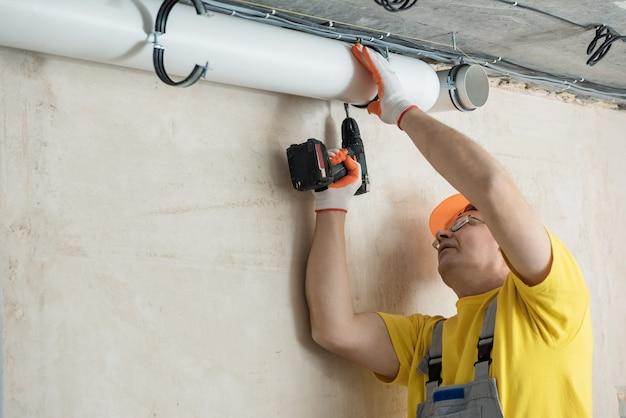 Pracownik przykręca śrubokrętem rury wentylacyjne do sufitu.