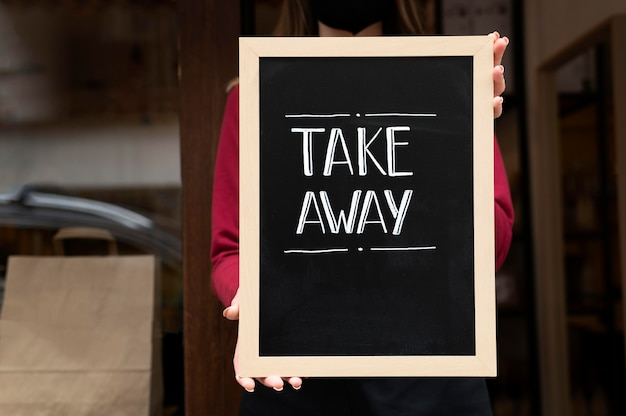 Pracownik restauracji umieszczający znak na wynos przed restauracją?