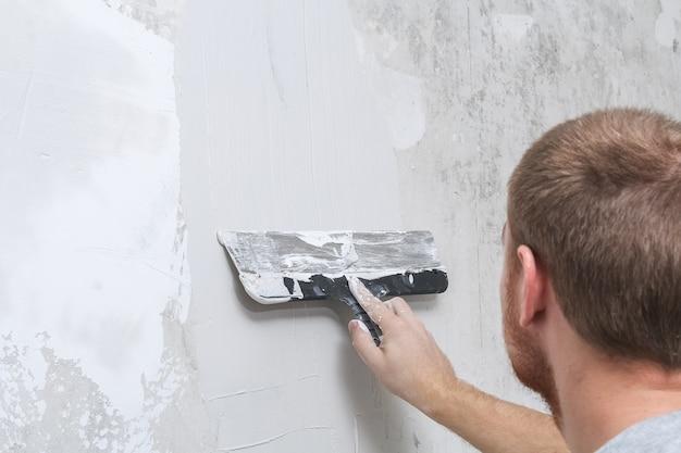 Pracownik rozprowadza masę szpachlową i wyrównuje ścianę
