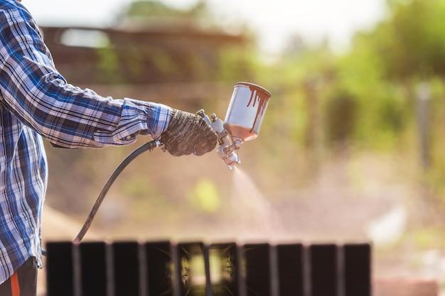 Pracownik rozpylający farbę na stalową rurę, aby zapobiec rdzy na powierzchni