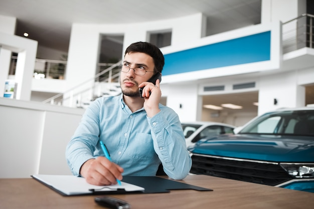 Pracownik salonu samochodowego rozmawia przez telefon i pisze