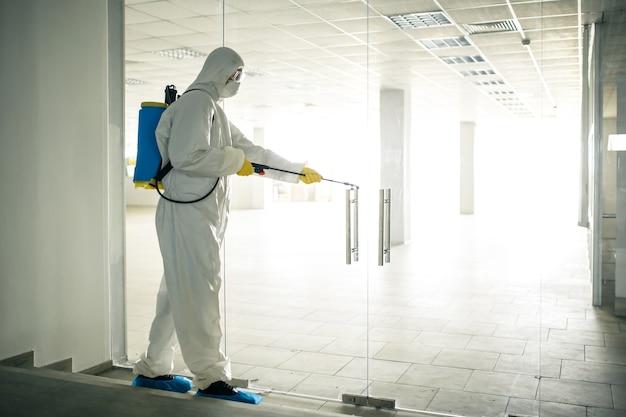 Pracownik sanitarny spryskuje puste centrum biznesowe płynem antyseptycznym, aby zapobiec rozprzestrzenianiu się covid-19. mężczyzna ubrany w garnitur do dezynfekcji sprzątający centrum handlowe. nikt, zdrowie, odizolowane pojęcie.