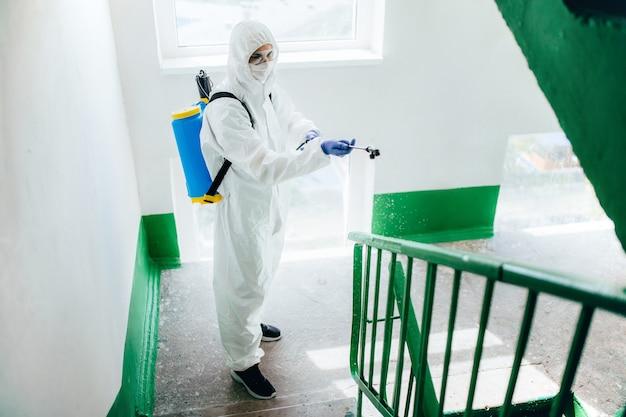 Pracownik sanitarny w kombinezonie ochronnym dezynfekuje blok mieszkalny klatki schodowej. środki zapobiegania koronawirusowi na obszarach mieszkalnych.