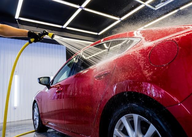 Pracownik serwisu mycie samochodu na myjni samochodowej.