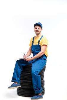 Pracownik serwisu opon siedzi na stosie opon, biały, mechanik, montaż kół