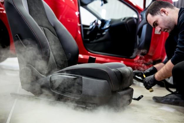 Pracownik serwisu samochodowego czyści fotelik samochodowy za pomocą myjki parowej
