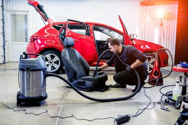 Pracownik serwisu samochodowego czyści fotelik samochodowy za pomocą odkurzacza