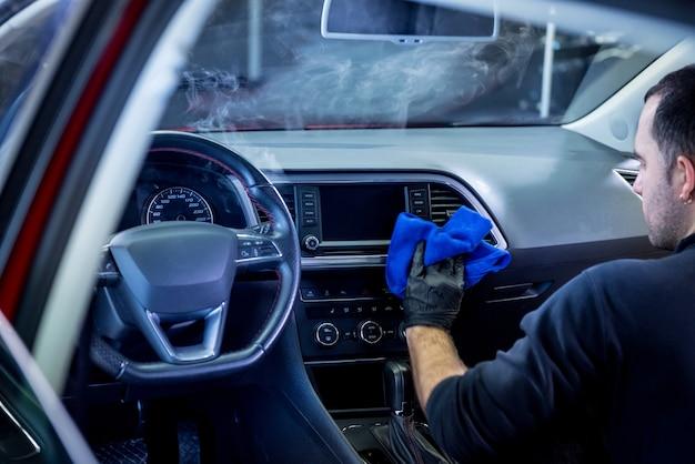 Pracownik serwisu samochodowego czyści wnętrze odkurzaczem parowym