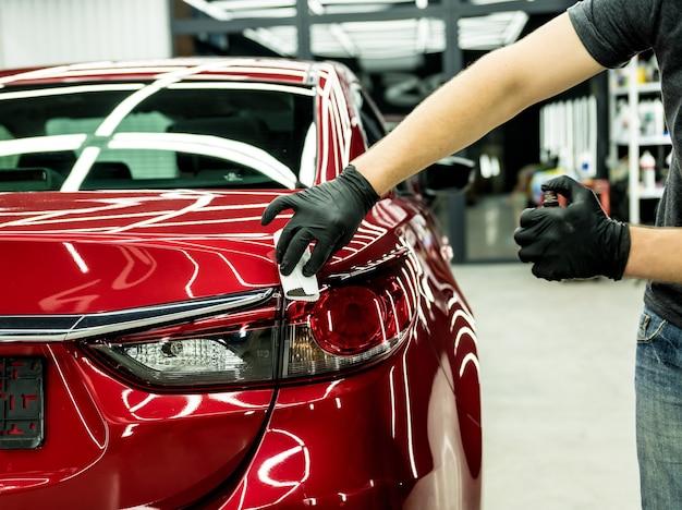 Pracownik serwisu samochodowego nakładający nano powłokę na samochód
