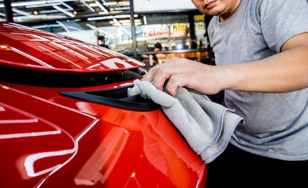 Pracownik serwisu samochodowego polerujący samochód ściereczką z mikrofibry.