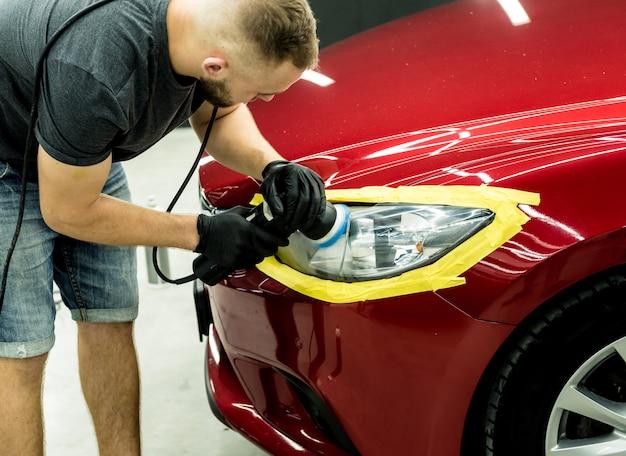 Pracownik serwisu samochodowego poleruje szczegóły samochodu za pomocą polerki orbitalnej.