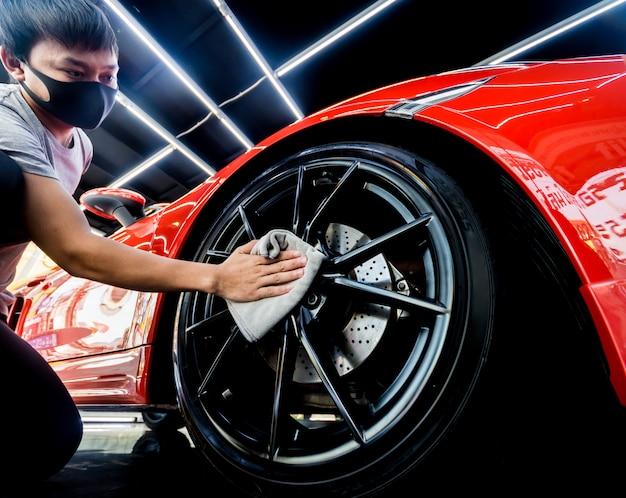 Pracownik serwisu samochodu poleruje koła samochodowe ściereczką z mikrofibry.