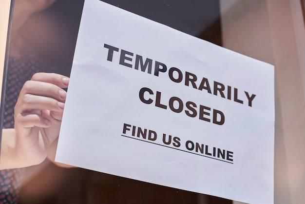 Pracownik sklepu lub restauracji wisi zamknięty znak