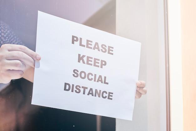 Pracownik sklepu lub restauracji wisi znak ostrzegawczy