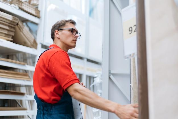 Pracownik sklepu podłogowego stojący przy regałach z płytą laminowaną