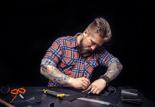 Pracownik skórzany produkujący skórzany przedmiot w swojej garbarni / rzemieślnik przy pracy nad swoim nowym produktem skórzanym.