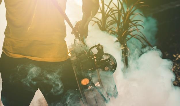 Pracownik służby zdrowia fumigacja zaparowuje komary nosiciele wirusa dengi zika lub malarii.