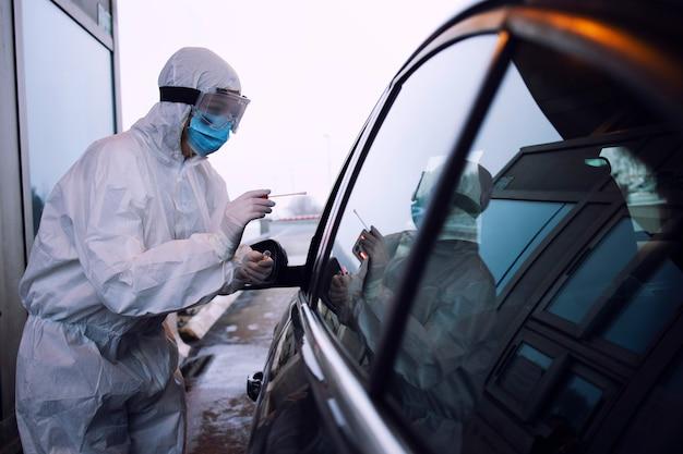 Pracownik służby zdrowia w białym kombinezonie ochronnym, rękawiczkach i masce na twarz, pobierający wymaz z nosa i gardła w celu zbadania pasażera na obecność wirusa koronowego.