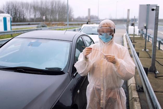 Pracownik służby zdrowia w białym kombinezonie ochronnym, stojący na przejściu granicznym, gotowy do testowania pasażerów na obecność wirusa koronowego.