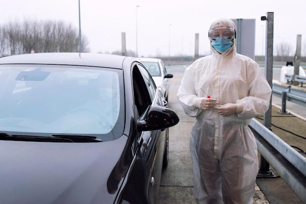 Pracownik służby zdrowia w białym kombinezonie ochronnym, w rękawiczkach, stojący na przejściu granicznym i trzymający zestaw testowy na obecność wirusa koronowego.