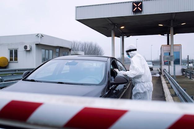 Pracownik służby zdrowia w białym kombinezonie ochronnym wykonujący wymaz z nosa na obecność wirusa koronowego na przejściu granicznym.