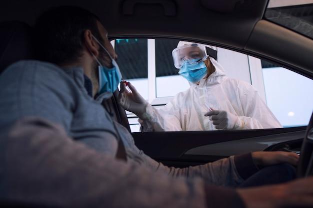 Pracownik służby zdrowia w białym kombinezonie ochronnym z rękawiczkami i maską na twarz pobierający wymaz z nosa i gardła w celu zbadania pasażera na obecność covid-19.