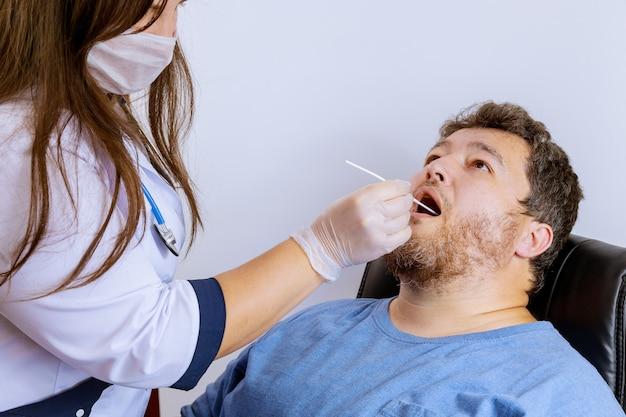 Pracownik służby zdrowia ze sprzętem wykonuje wymaz z jamy ustnej koronawirusa mężczyzna koronawirus covid-19.
