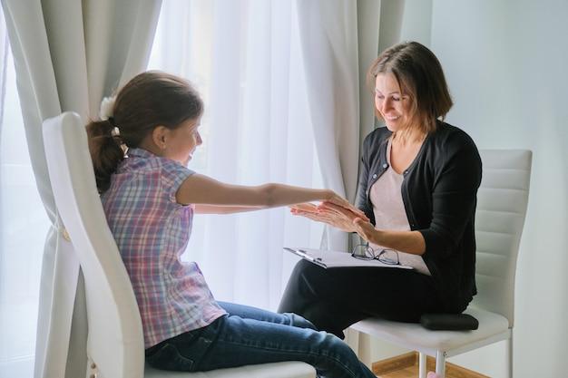 Pracownik socjalny kobieta mówi do dziewczynki psychologia dziecka, zdrowie psychiczne.