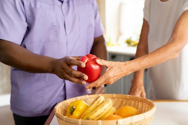 Pracownik socjalny przygotowujący jedzenie ze starszą kobietą