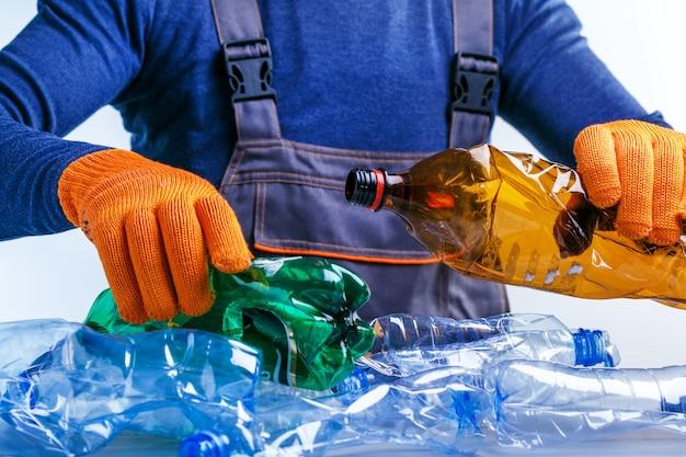 Pracownik sortuje śmieci plastikowe do recyklingu.